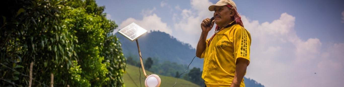 man charging phone from solar lamp